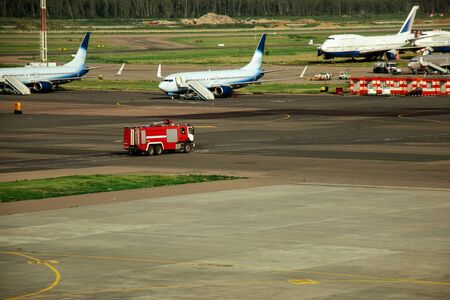 Fire truck on the runway near the aircraft. Airport Rescue Service. Firefighters and fire department at the airport. Crisis Response System 版權商用圖片