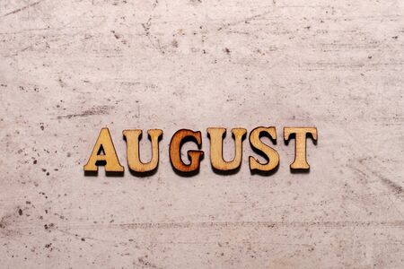 The word August laid out in wooden letters on a light background. Close-up. Summer time years and months of the year Stock fotó
