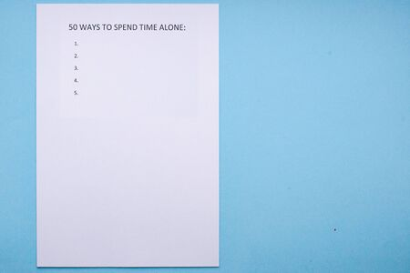 Caption 50 WAYS TO SPEND TIME ALONE on white sheet. White sheet on a blue background. Tree time planning