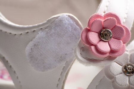 Velcro on childrens shoes close-up. White shoes with a pink flower. Safety and comfort Stock Photo