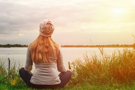 Beautiful girl with long hair is sitting on the shore. The view from the back. Sunset. Peace and tranquility. Yoga by the lake.