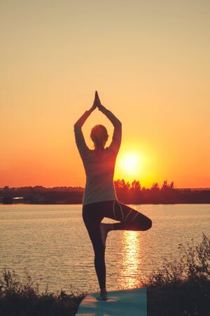 Una niña está de pie en el lago al atardecer, haciendo yoga. Se para en una pose de árbol de Sathi Yoga. Equilibrio, armonía, equilibrio, concentración, relajación Foto vertical. Foto de archivo