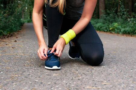 Young tanned blonde girl runner tying shoelaces, getting ready for a run. The concept of a healthy lifestyle, freedom. Stock fotó