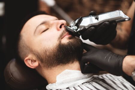 Radersi la barba in un negozio di barbiere con un rasoio pericoloso. Cura della barba da barbiere. Asciugare, tagliare, tagliare la barba. Messa a fuoco selettiva