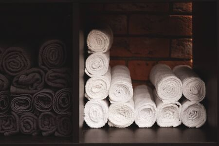 White towels folded into a roll. Brickwork in the background. Presentation of textiles. Rational use of space.