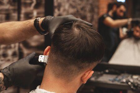 Testa di taglio di capelli nel negozio di barbiere. Il barbiere taglia i capelli sulla testa del cliente. Il processo di creazione di acconciature per uomo. Barbiere. Messa a fuoco selettiva Archivio Fotografico