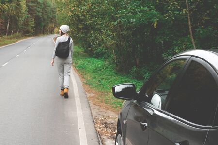 A young woman with a backpack behind him is walking along an empty autumn road. Travel, hipster. Walk in the fall, autumn trees