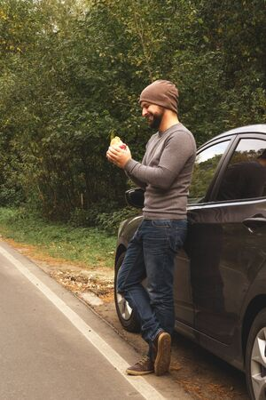 Young guy eating a burger near a car on an empty road. Food on the trip. Food on the go. Autumn travel. Fast food