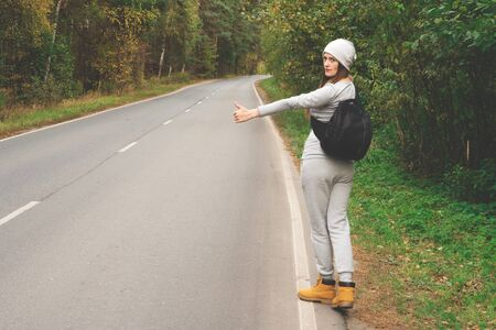 A young and beautiful girl votes on the road. Autumn road. Catch a car on an empty road. Hitchhiking. Free travel by car