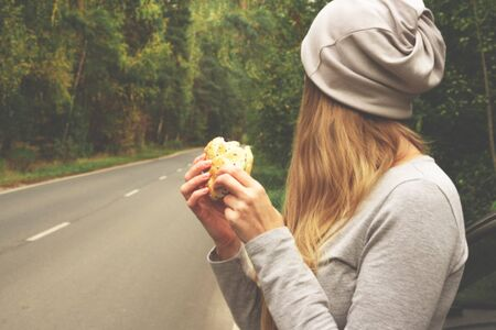 A young woman is eating a burger near a car on an empty road. Food on the trip. Food on the go. Autumn travel. Fast food Imagens