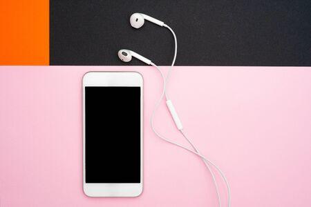 Musik, Gadgets, Musikliebhaber. Weißes Smartphone und Kopfhörer auf den orangefarbenen, schwarzen und weichen rosa Hintergründen mit Kopfhörern. Sicht von oben. Flache Lage, Ansicht von oben Standard-Bild