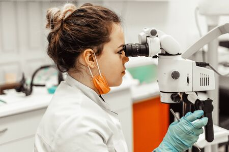 Young woman dentist doctor looks through a professional microscope in a dental clinic. A doctor in a disposable medical mask and cap. Advanced equipment in dentistry
