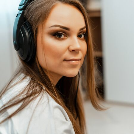 Listening to music. Young beautiful girl with big headphones on her head. Close-up. Leisure and music. Imagens