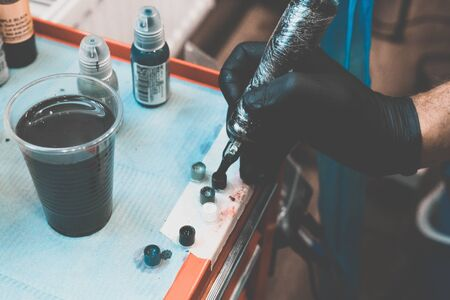 Tattoo salon. Tattoo machine and prepared paints for tattoos on the table. The process of curing paint. Close-up, tinted, tattooist. 写真素材