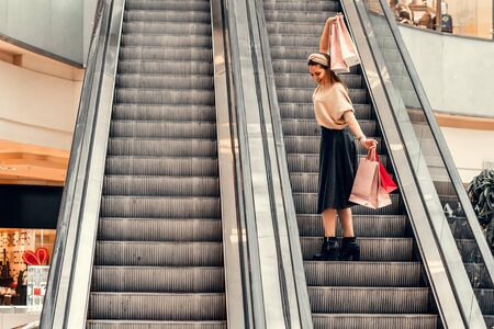Two girls on an escalator in a shopping center. In the hands of paper bags. Shopping, leisure and entertainment.