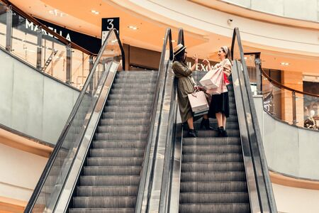Two girls on an escalator in a shopping center. In the hands of paper bags. Shopping, leisure and entertainment