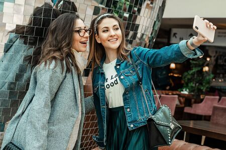 Trade, buyers. Two beautiful girls make purchases in a shopping center, go shopping. They look at the smartphone, take a selfie. The joy of consumption.