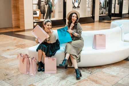 Girls are resting on the couch in the mall. Shopping, entertainment and leisure. Break in purchases.