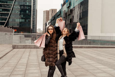 Shopping, consumption. Office center, glass buildings. Two beautiful girls are walking on the street with paper bags from shops. Shopping in the quarter of skyscrapers. Entertainment of modern women.