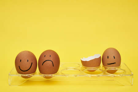 Chicken eggs in an egg holder. Full tray of eggs. Half an egg, egg yolk, shell. Emotion and facial expression painted on eggs