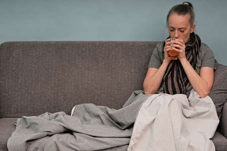 The girl is sick at home. Sitting on a couch, wrapped in a blanket, a scarf around his neck. Drinks hot tea. Coronavirus.