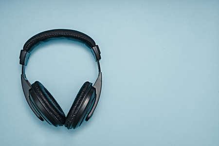 Large, black headphones lie on a colored background. Device for individual listening to music Banque d'images