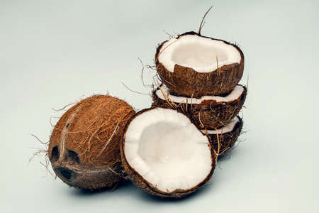Parts of coconut on a colored background. Close up. Fresh ripe coconut broken into pieces. Stockfoto