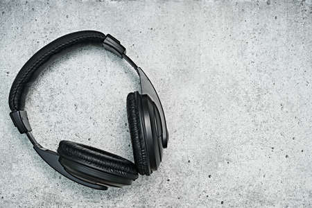 Large, black headphones lie on a colored background. Device for individual listening to music