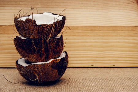 Parts of coconut on a colored background. Close up. Fresh ripe coconut broken into pieces. Stock Photo