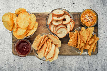 Mix of chips, snacks and crackers on a wooden stand. Unhealthy food, beer snack, ready meal. Close Up.