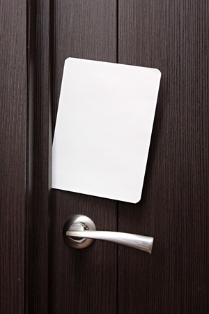 slipped: white envelope with message slipped under wooden door. Blank paper to write a nested in the gap under the wooden door.