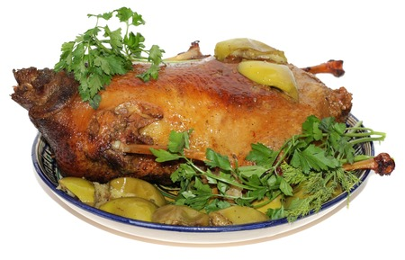 christmas goose: goose baked with apples. Christmas goose or Turkey baked. On the plate, isolated on white .