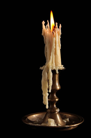 burning: Burning Candle In Old Silver Candlestick Isolated on Black Background. Stock Photo