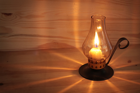 burning candle in the glass tube against a wooden wall.