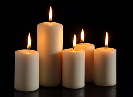 six burning candles on a black background. Imagens