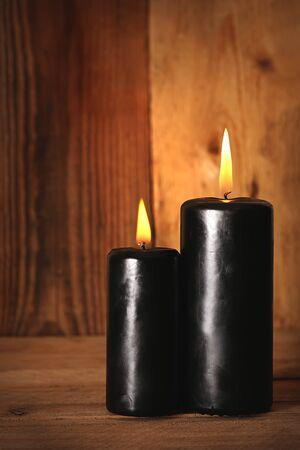 vigil: Black burning candles  wooden background. Symbols of witchcraft. Halloween