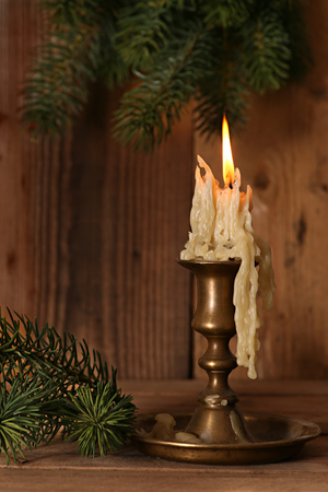 Burning old Candle Vintage Bronze candlestick on wooden background. Spruce branches. Christmas background. Stock Photo