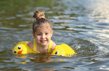 水泳、水、ビーチ リゾート、夏の休暇や休日の概念で楽しんで幸せな子かわいい女の子のポートレート、クローズ アップ
