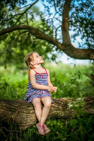 45 years old: child Girl of 4-5 years old , sitting on branch of tree, happy face, looking up at sky.