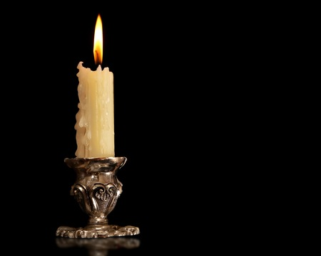 burning old candle vintage Silver bronze candlestick. Isolated Black Background.