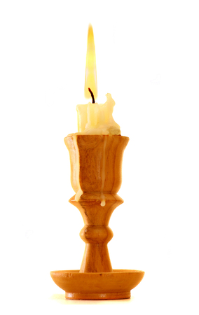 burning old candle vintage wooden candlestick. Isolated on white background.