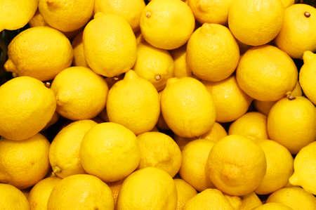 Lemon, orange, fresh fruit mix as background, top view. fresh citrus fruit market. A pile of oranges sitting on top of a wooden table