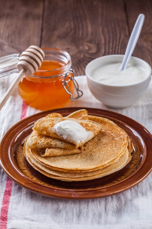 A stack of pancakes with sour cream and honey for Maslenitsa