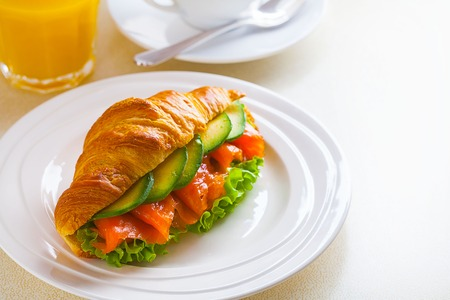 croissant sandwich with salmon and avocado, coffee and orange juice on a white background
