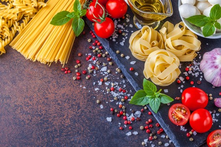 Ingredients for pasta with mozzarella and tomatoes on a dark background, horizontally with a notepad for writing