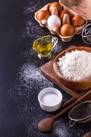 bakery products: Ingredients for cooking bread on a dark background vertically
