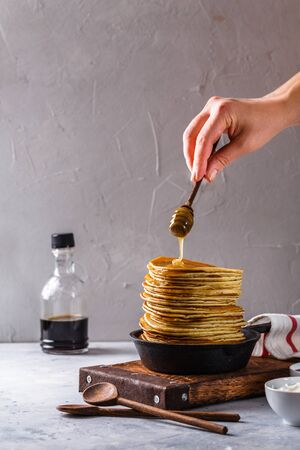 Pancakes with honey in a cast-iron frying pan on a black background, vertically, copyspace