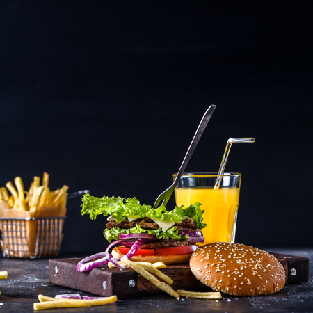 hamburger on a black background with French fries and orange juice, horizontally, square, wooden board, copyspace Stok Fotoğraf