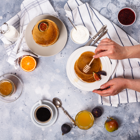 Pancakes with honey, fruit and coffee on a gray background, square, figs, alginate juice, raspberry jam, sour cream, flat lay, copyspace