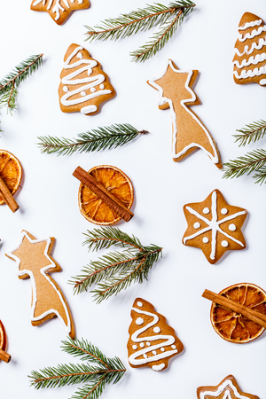 flat lay of Christmas cookies, dried orange and fir branches on a white background, vertically